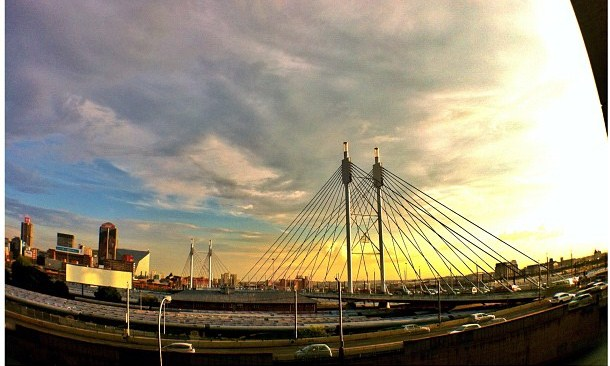 A photo of Nelson Mandela Bridge in Johannesburg. The sky is blue and yellow.
